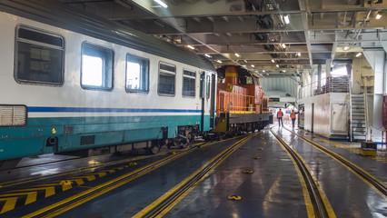 si apre il portellone e gli operai consentono l'uscita del convoglio ferroviario dalla nave traghetto