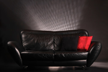 black leather sofa with red and black pillow