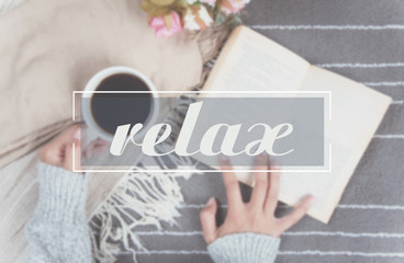 relax text and woman hand holding coffee cup of hot drink and read a book on gray carpet.