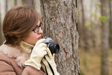 young woman taking photo in the forest