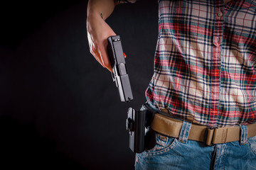 woman wearing jeans takes out a pistol from the holster