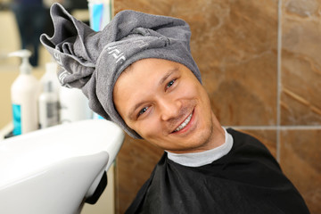 Portrait of funny handsome smiling man with towel