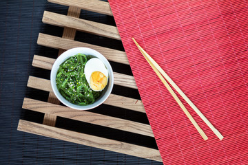 Hiyashi wakame with sesame and nut sauce, boiled egg in ceramic bowl and bran bread on the rustic wooden lattice, black and red makisu
