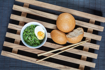 Hiyashi wakame with sesame and nut sauce, boiled egg in ceramic bowl and bran bread on the rustic wooden lattice and black makisu