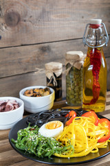 Hiyashi wakame with sesame and nut sauce, black and corn noodles, boiled egg. Octopus and mussels in ceramic bowls, bottle of olive oil with chili pepper, black olives and capers in jar, bran bread