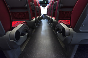 Bus seats in row with red leather, textile coating, wooden armrests and mounts for safety belts, rear view, modern comfortable tourist transport interior, selective focus