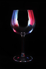 Nightclub wine glass lit by red, blue, lilac party lights isolated on black background, nightlife