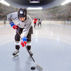 Junior Ice Hockey Player Puck Handling in Arena With Copy Space.