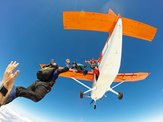 A group of skydivers friends jumping from the orange plane