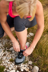 sporty woman tie shoe ona a path outdoor before running