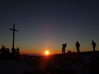 Silhouette of photograph is taking some photograph on mountain. A Crucifix In Front Of A Sky.
