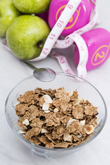 cereals or muesli with tape measure and weight, diet and exercise concept