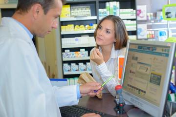Female customer talking to male pharamacist