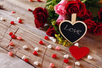 Red hearts and roses on wooden table