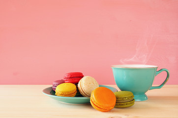 Cup of coffee and colorful macaron on wooden table