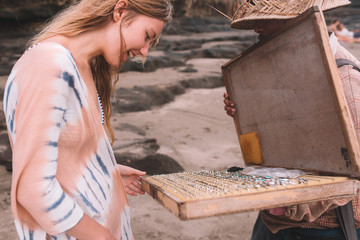 Blonde hair girl choosing the silver ring on the beach