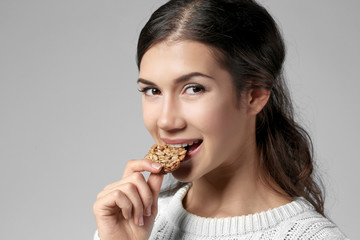 Pretty young woman eating tasty cookie, on grey background