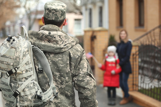 Soldier returning from war with blurred family on background