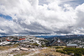 Helipad at the house at the top of rugged mountains in the Alps in the background of the sky, cumulus clouds tightened.