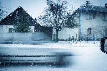 Winter Scene Through Car Window. Blurred Motion Vehicle on Street Covered with Snow. Houses on Background.