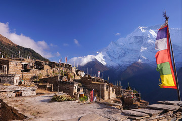 Traditional nepalese village on Pisang region with buddhist praying flags and North Face of Annapurna II mountain summit on background, Annapurna Circuit Trek, Himalaya, Nepal, Asia. horizontal view