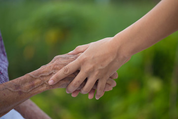 Old and young holding hands on light background, closeup