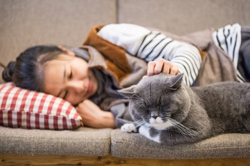 Girl and cat sleeping on the couch