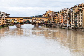 Ponte Vecchio over Arno River and houses in autumn