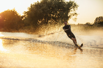 Wakeboarder surfing across the lake Wall mural