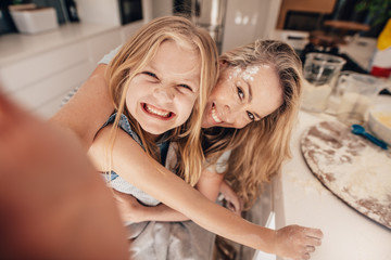 Smiling little girl and woman in kitchen taking selfie