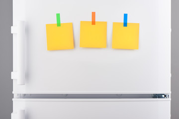 Yellow paper notes attached with stickers on white refrigerator