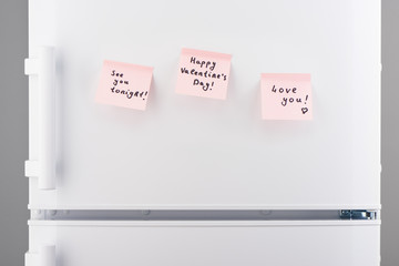 Love notes on light pink sticky paper on white refrigerator