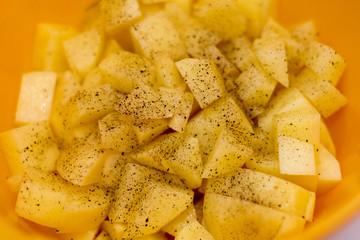 Cut raw potatoes in bowl