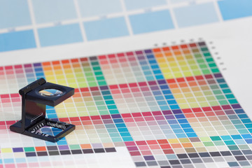 Magnifier or printer's loupe sits on a colorful CMYK test sheet