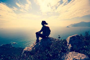 young woman hiker at sunrise seaside mountain peak