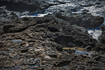 Rough rocky surface on shore with white foam of sea water. Scene lit with sunlight. Natural ocean cost pattern wet stone textures.