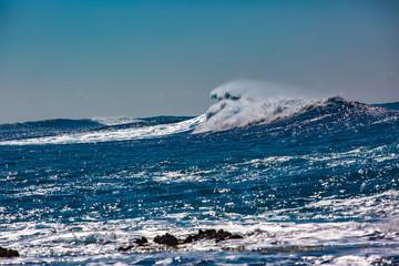 Rough blue ocean wave crashing. Black rocks showing up from white foam.