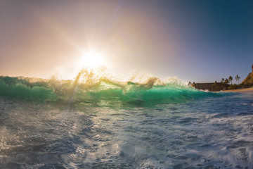 Breaking transparent clear ocean wave with green shining water lit with sunset sunlight at tropical hawaiian beach