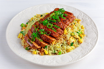 Chinese style Egg fried rice with sliced pork fillet on white wooden table.