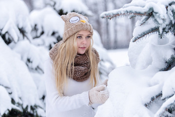 Attractive smiling young blonde girl walking in winter forest. Pretty woman in wintertime outdoor. Wearing winter clothes. Knitted sweater, scarf, hat and mittens.