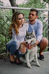 Beautiful young couple playing with a dog husky in a park. Summer outdoors.