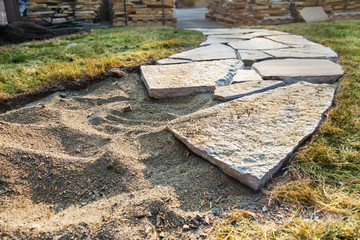 Fotobehang - Sand base of path with a few stones placed; piles of pavers in the background