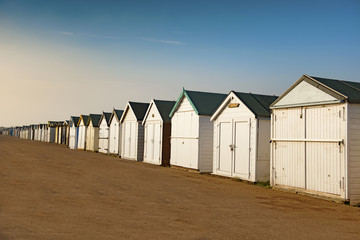 Beach huts in Shoeburyness, Essex. Photograph taken during the golden hour. The huts are closed and locked up as it is out of holiday season