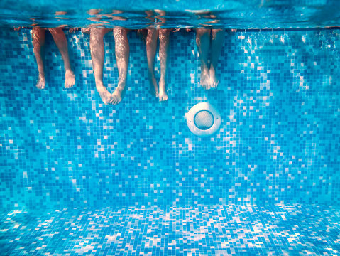 Children's and adults legs underwater in swimming pool