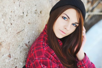 Portrait of a serious beautiful girl with blue eyes, wearing a Red shirt and hat on the background of a concrete wall, close-up