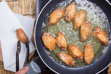 Chef frying chicken wings in pan