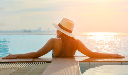 Young woman in big hat relaxing on the swimming pool, near the sea in the sunset Wall mural