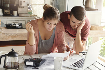 Young married couple with many debts doing paperwork together, reviewing their bills, planning family budget and calculating finances at kitchen table with papers, calculator and laptop computer