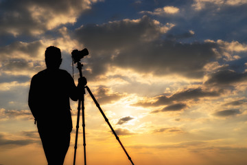 photographer silhouette with accessories and holding hand on tripod , taking pictures of the beautiful moments during the sunset ,sunrise