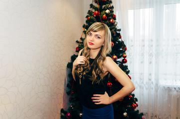 Beautiful blonde near a Christmas tree.